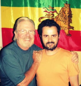 Richard Twine and Tom Regan standing together, smiling at the camera standing in front of brightly coloured flag.