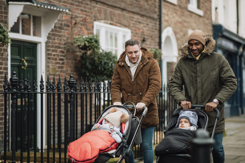 Two male friends are out in Tynemouth, North East UK. They are walking on a sidewalk and pushing their baby sons in strollers. They are wearing warm clothing.