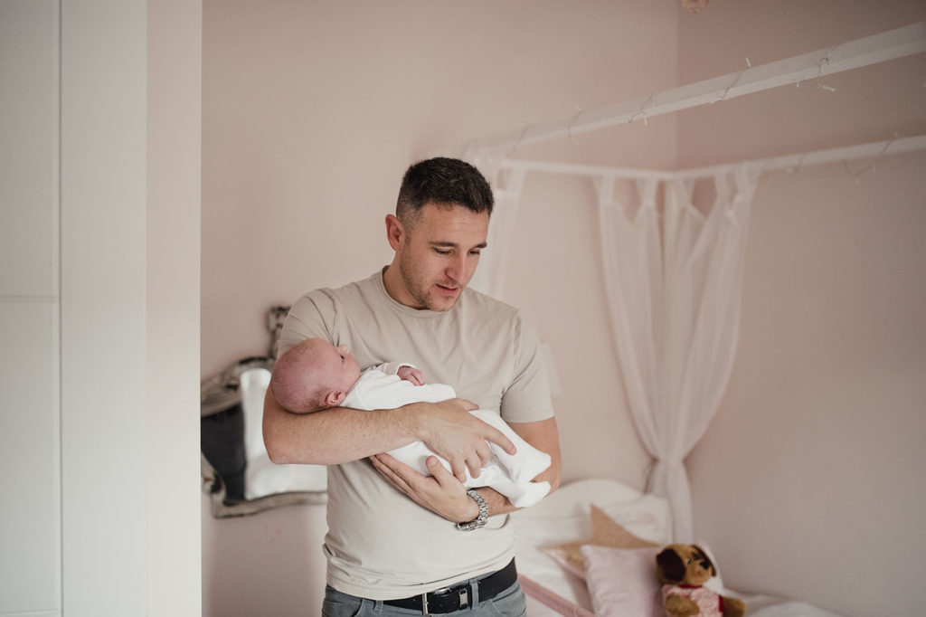 A father standing in his daughters room holding his baby.