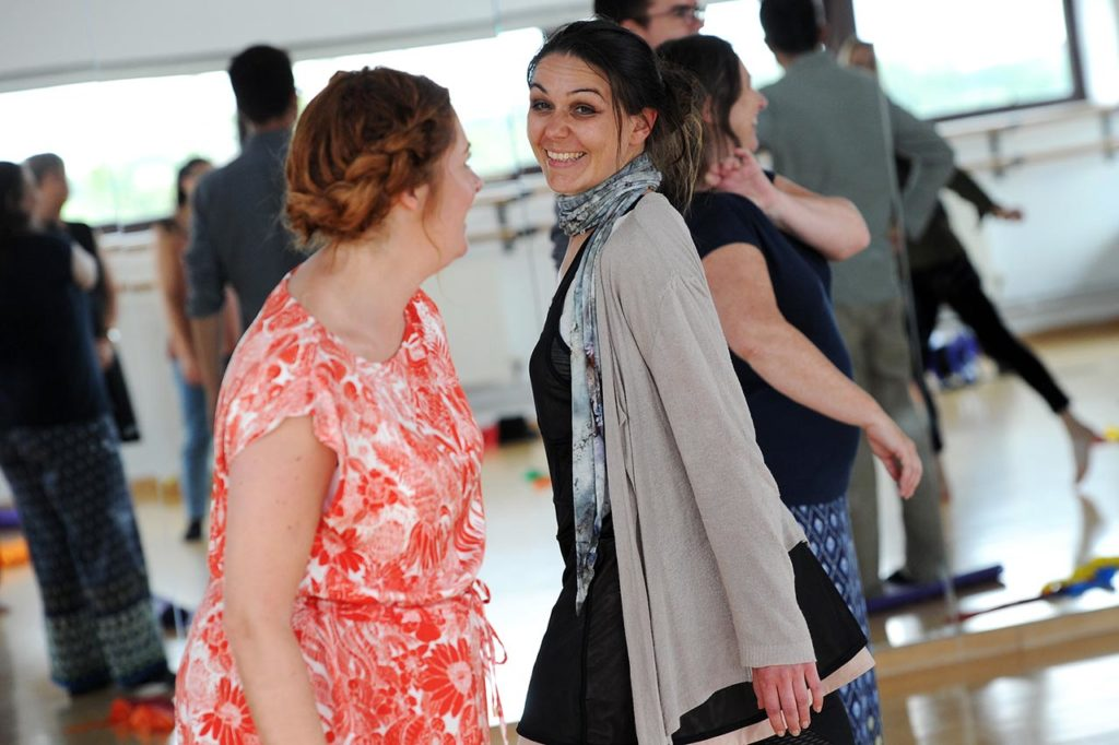 two women dancing while smiling at each other